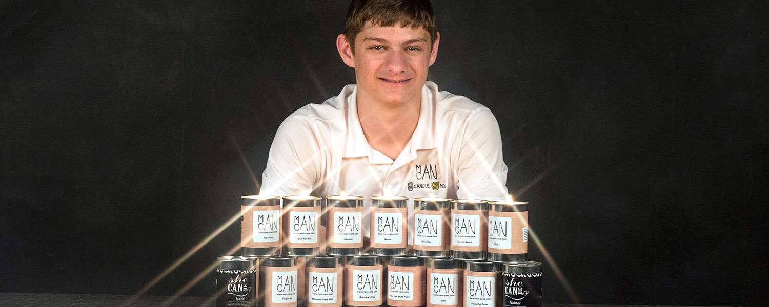 Kent State student Hart Main displays ManCans, masculine-scented candles he created. Part of the proceeds from each candle is donated to soup kitchens, and the candles themselves are made by individuals with development disabilities.