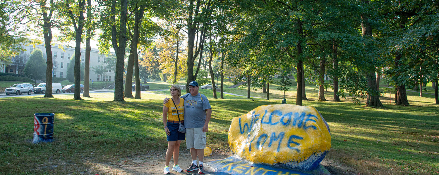 A couple stands next to the freshly painted rock on Front Campus near the Kent State Alumni Homecoming tent.