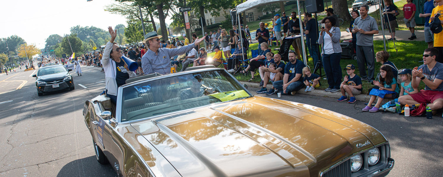 Kent State President Todd Diacon and his wife, Moema Furtado, ride down Main Street in a 1969 Oldsmobile. Diacon serves as this year's Homecoming Grand Marshal.