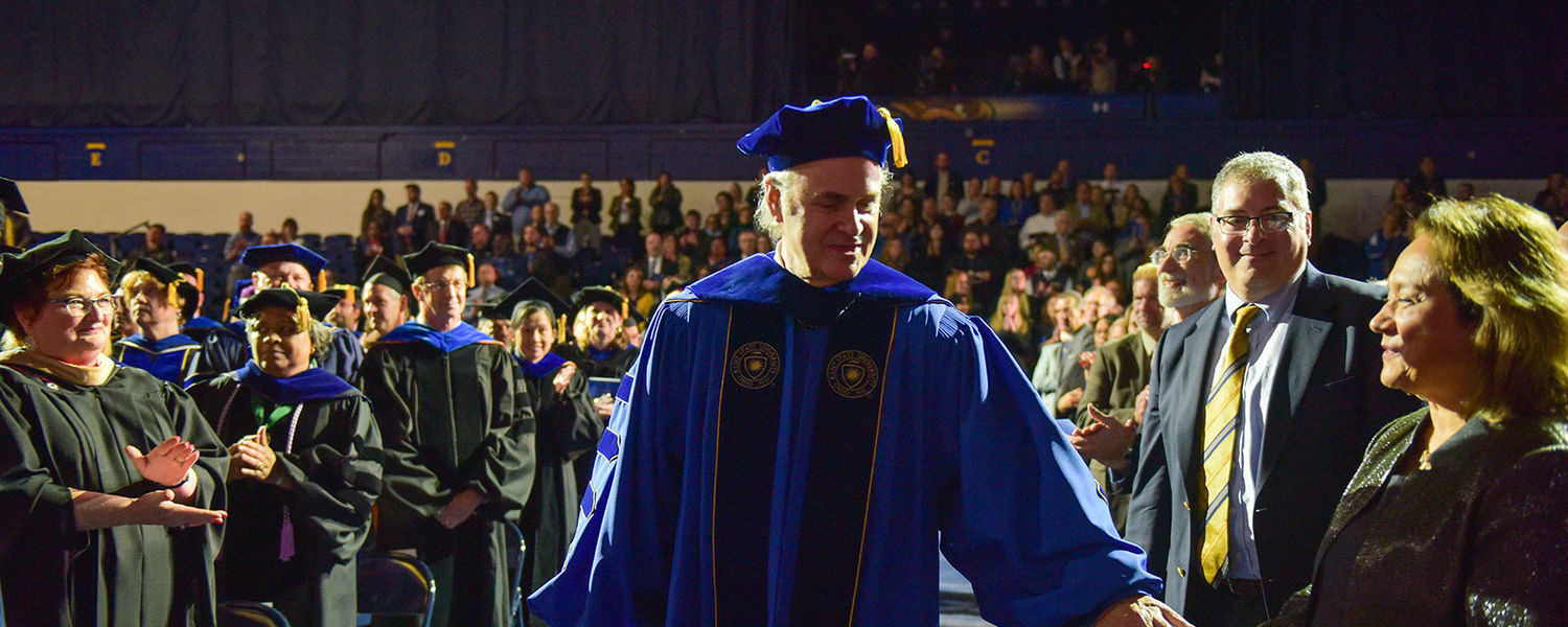 Kent State President Todd Diacon greets his wife, Moema Furtado, as he makes his way to the stage during his presidential inauguration.