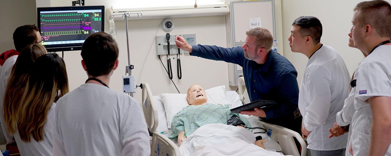 Jeremy Jarzembak explains a simulation mannequin's vitals to students