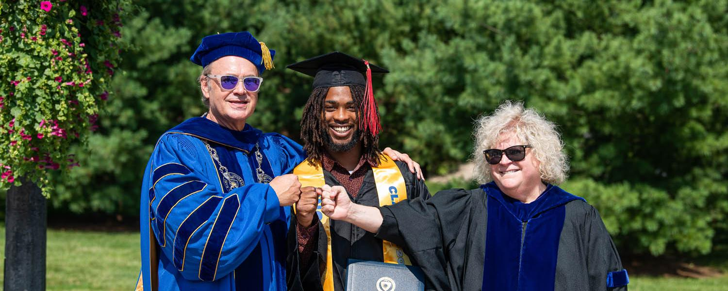 Kent State President Todd Diacon, a new graduate and Kent State Senior Vice President and Provost Melody Tankersley fist-bump after the undergraduate degree commencement ceremony.