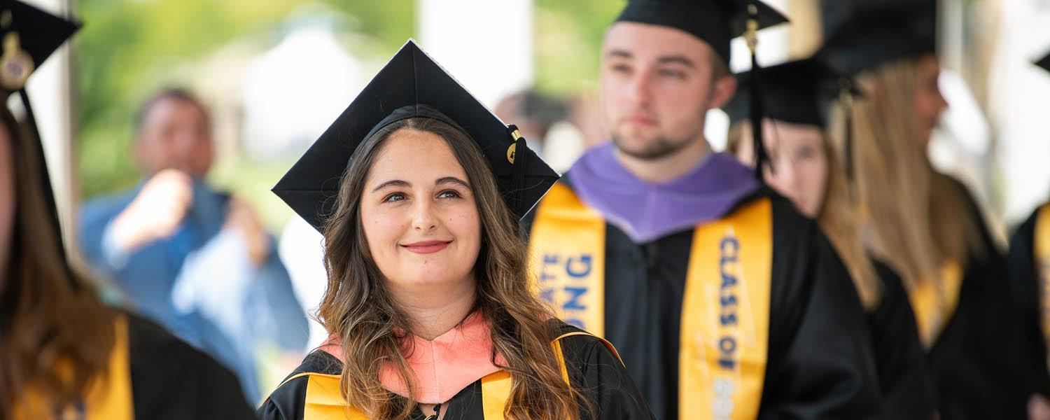 New Kent State graduates line up to walk across the stage and to accept their degrees during the advanced degree commencement ceremony.
