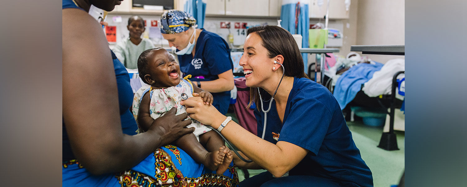 Nurse Shannon Gardiner examines a ticklish patient in the ward of the Africa Mercy in Guinea, West Africa.