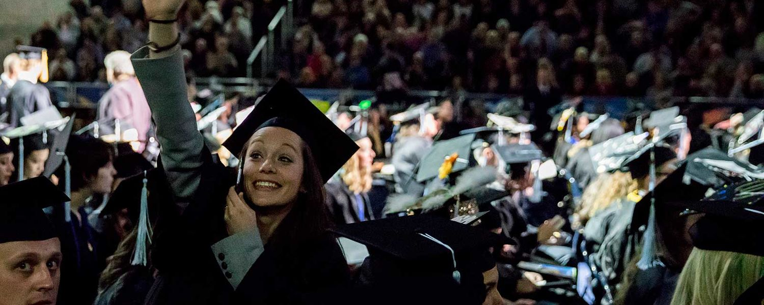 A new Kent State graduate waves to her family before her Commencement ceremony.