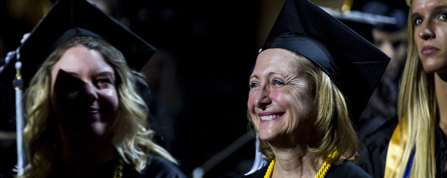 A Kent State staff member and graduate stands to be recognized during the morning Commencement ceremony for fall 2017.
