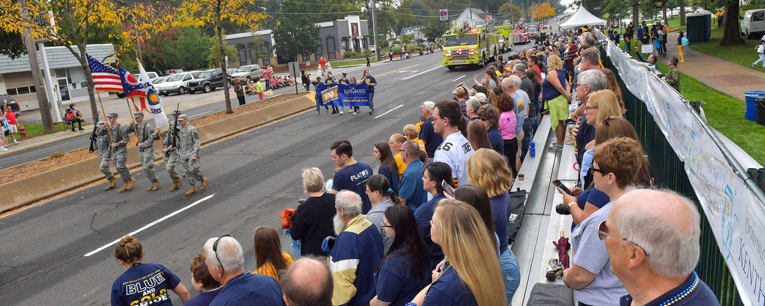 The crowd watching the Homecoming Parade stands as the American flag is carried by ROTC cadets.