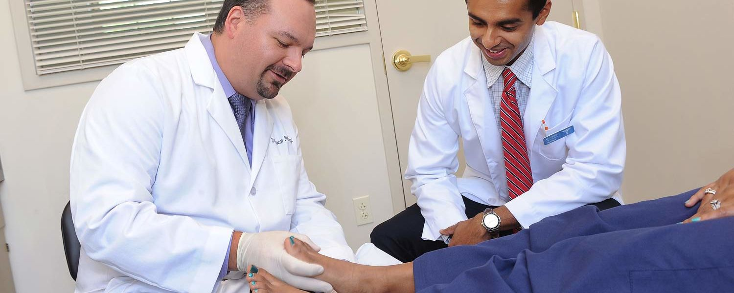 A student (right) at Kent State's College of Podiatric Medicine learns a medical procedure from an adjunct faculty member who is a working podiatrist.