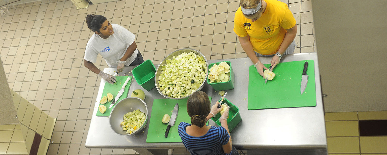 Kent State students chop vegetables in the kitchen in Beall Hall as part of the Campus Kitchen at Kent State.