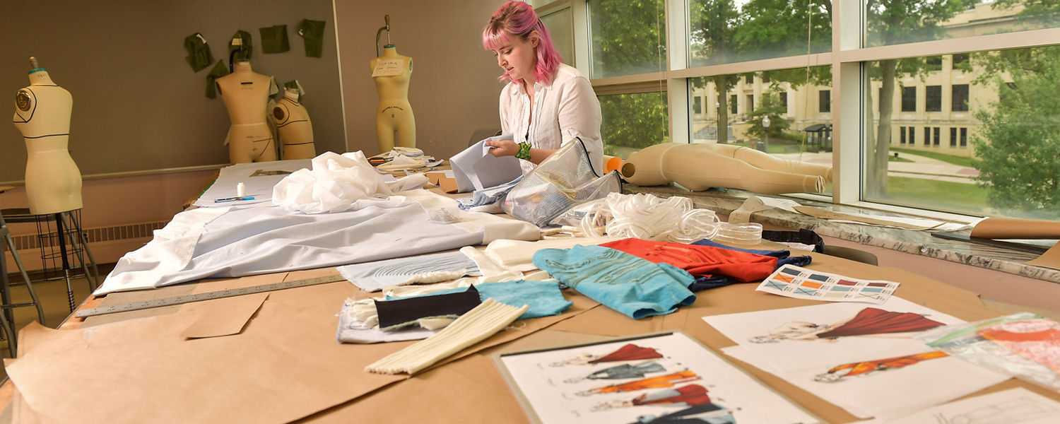 A Kent State University fashion design student works on a collection.