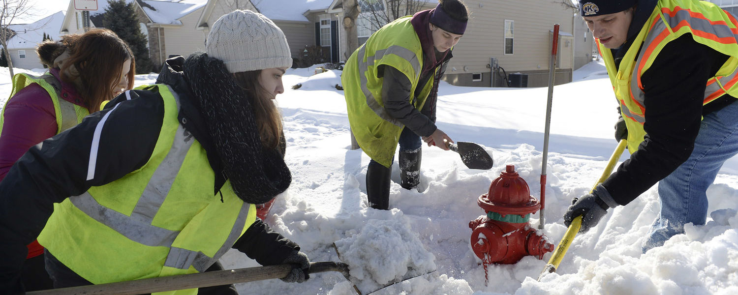 Kent State students and a staff member work to clear snow from around a fire hydrant in the city of Kent. The effort was organized by WKYC Channel 3 in Cleveland working with the Kent Fire Department.