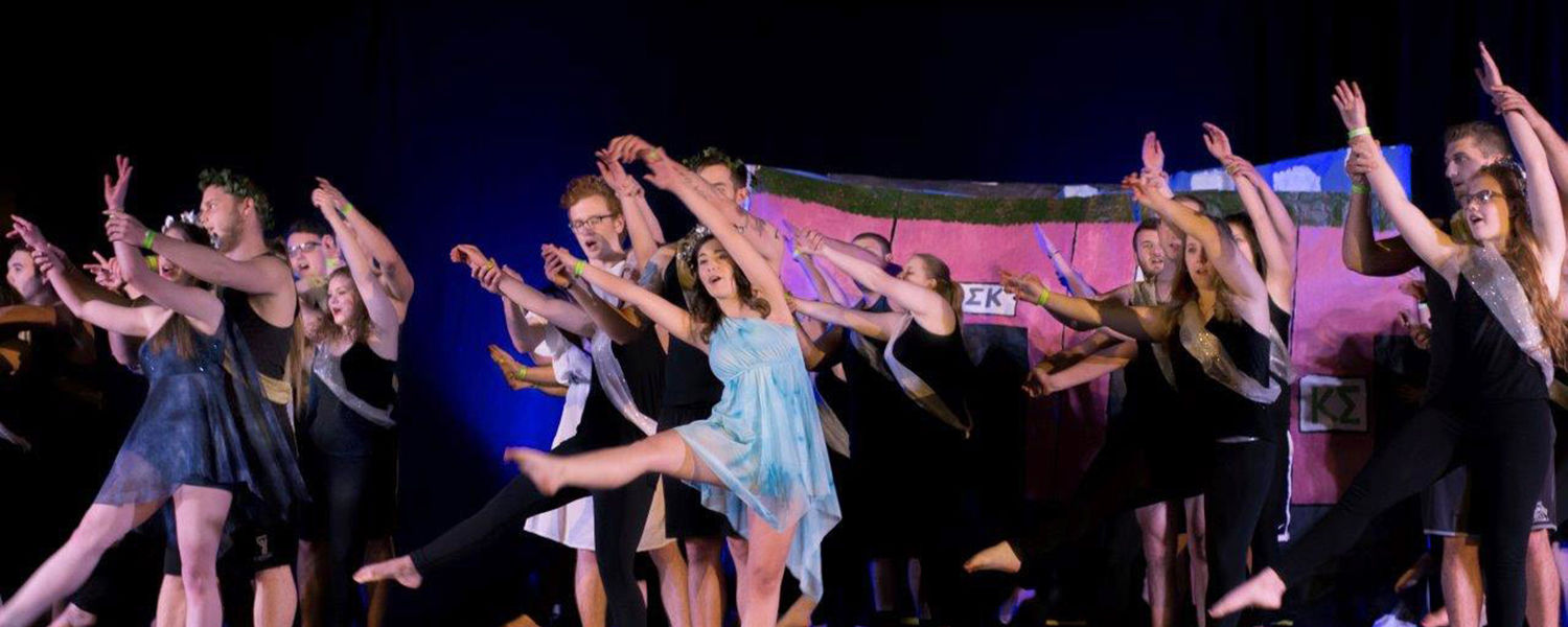 Members of Kappa Sigma, Phi Sigma Kappa, Sigma Phi Epsilon and Sigma Sigma Sigma dance in sync in front of a the crowd at Songfest, which was held in the MAC Center. (Photos courtesy of Signum Design)