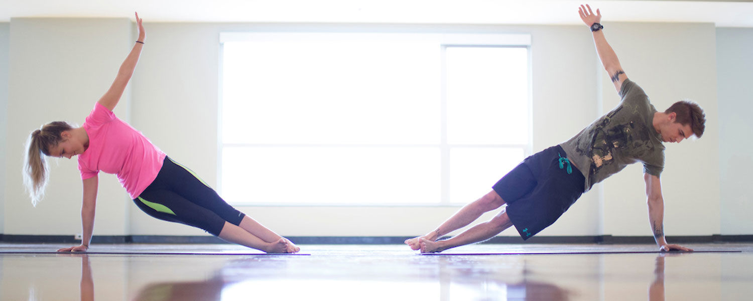 Female and male students in side plank yoga pose