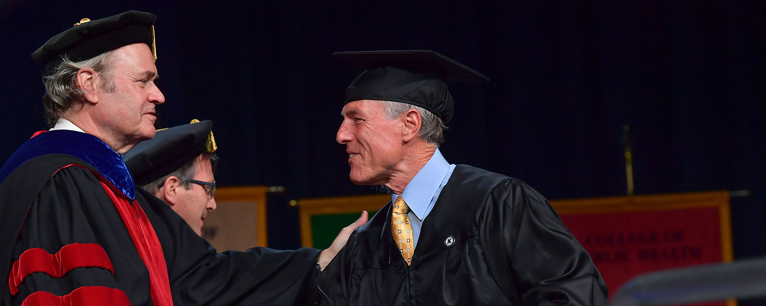 Todd Diacon, Kent State's executive vice president and provost, congratulates Rudd (Ted) Bare II during Summer 2018 Commencement.