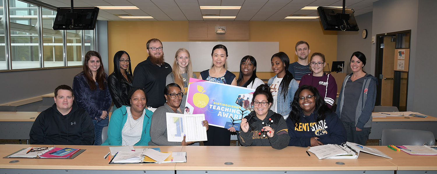 Zhiqiang Wang, Ph.D., associate professor of chemistry and biochemistry, earned a 2017 Distinguished Teaching Award. Dr. Wang is pictured with some of her students following a surprise classroom visit notifying her that she won the award.