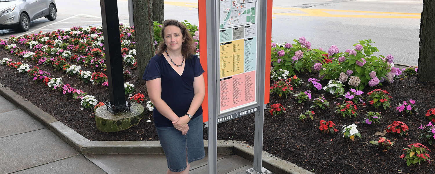 Kent State University Assistant Professor Jennifer Mapes, Ph.D., poses beside a map kiosk in downtown Kent that she helped to create.