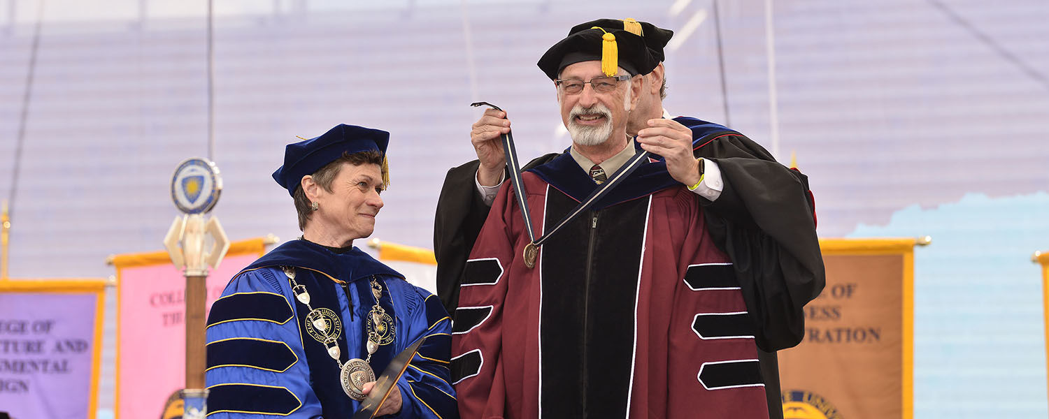 Todd Diacon, Kent State University's senior vice president for academic affairs and provost, places the President's Medal on Distinguished Professor of Human Evolutionary Studies C. Owen Lovejoy as Kent State President Beverly Warren watches.