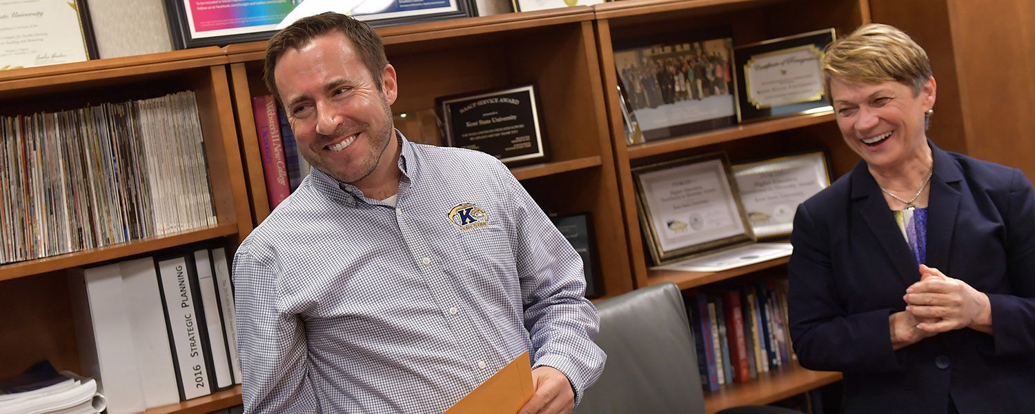 Kent State University President Beverly J. Warren recently presented 11 Kent State staff members with the President's Award of Distinction. Here, Ken Ditlevson, director of Kent State's LGBTQ Student Center, is surprised with his award.