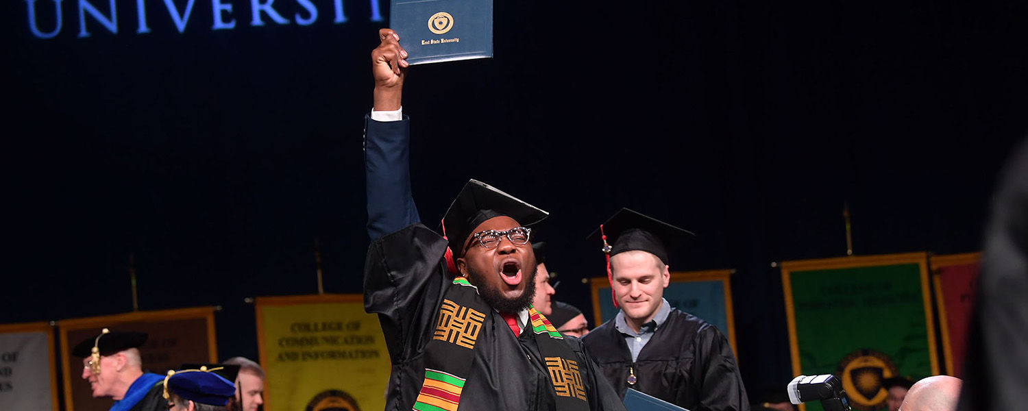 A Kent State University graduate celebrates as he crosses the stage during his Commencement ceremony.