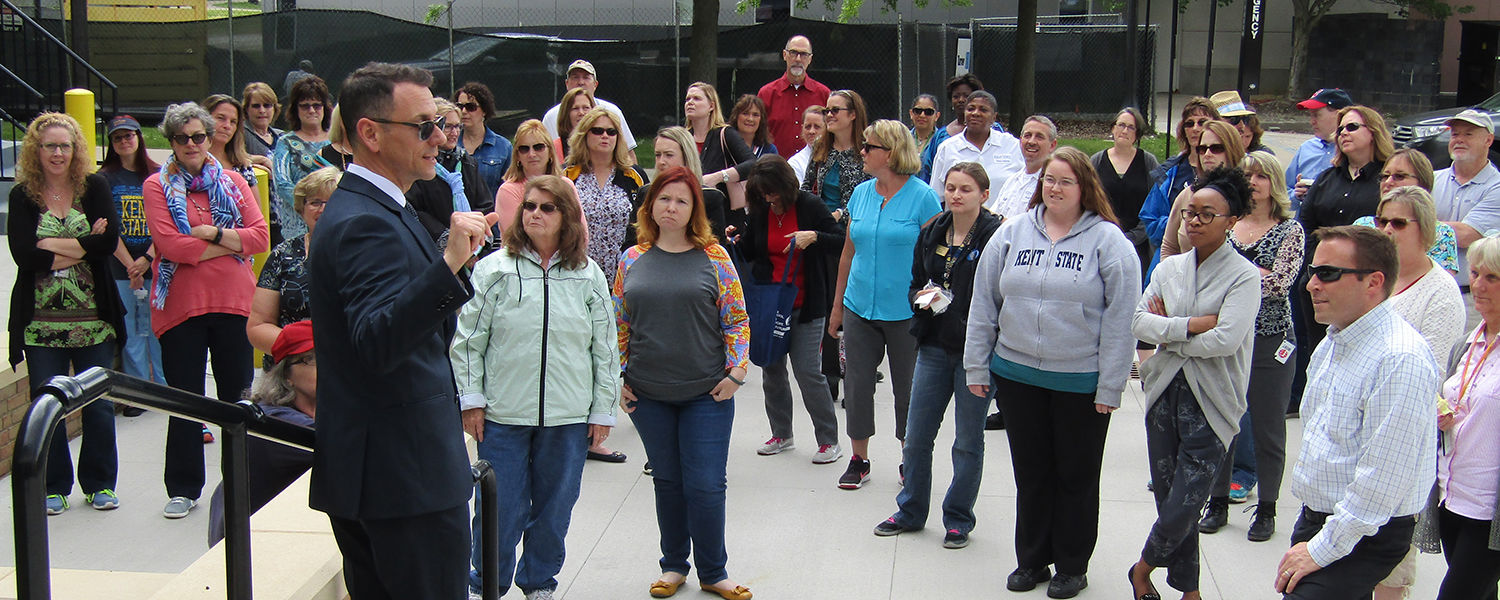 Kent State employees pause to listen to Michael Bruder, executive director of facilities planning and design, during a Walk and Talk to learn about campus construction.  The Walk and Talk is one of Kent State's wellness initiatives for employees.