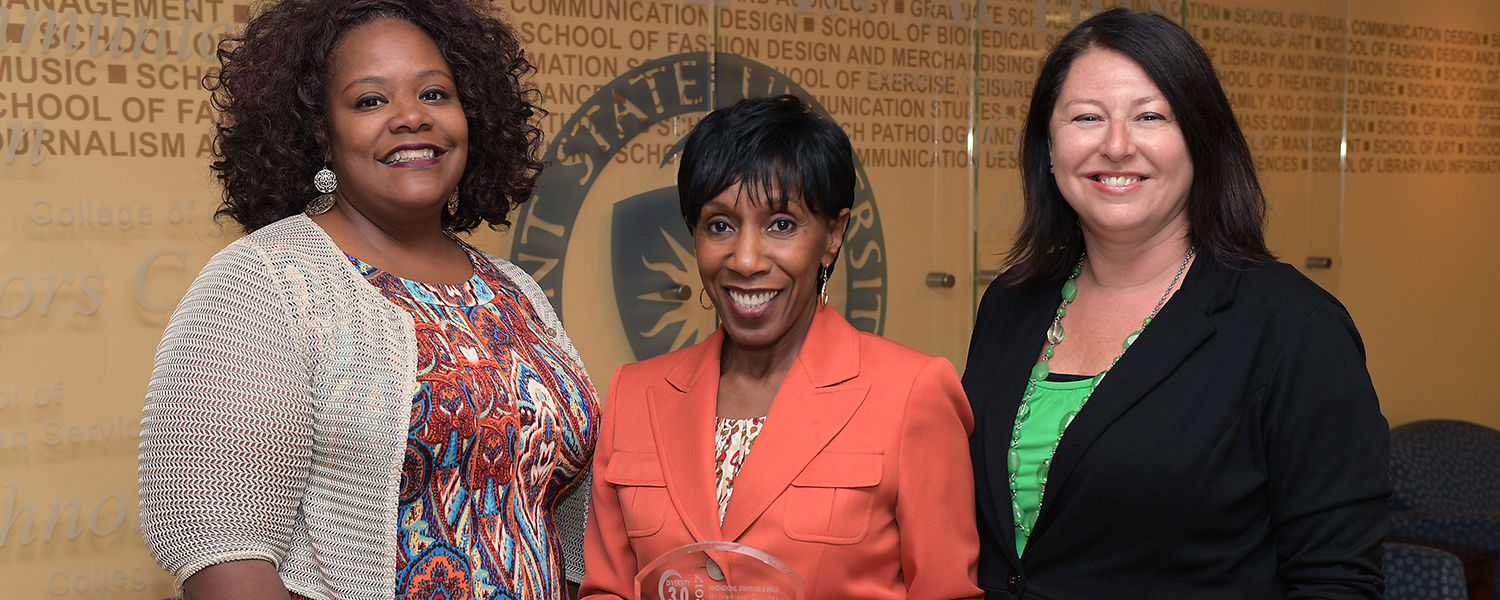 Lisa Givan (left), Alfreda Brown (middle) and Dana Lawless-Andric, all from Kent State's Division of Diversity, Equity and Inclusion, display the Innovation + Inclusion Leadership Award that was presented to the university.