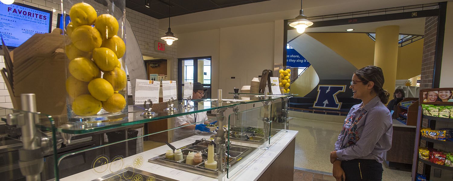 A Kent State employee looks on as a Dining Services' staff member prepares the new Golden Flash Bistro for the start of the fall semester. Golden Flash Bistro, formerly Kent Market I, will feature Olilo by Cat Cora, renowned celebrity chef.