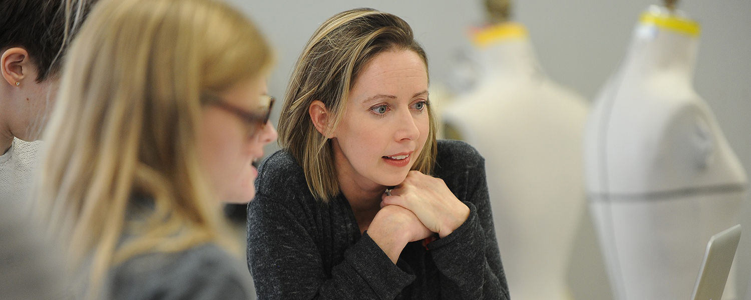 Sara Snyder, assistant professor in Kent State University's Fashion School, confers with a fashion design student on a project.