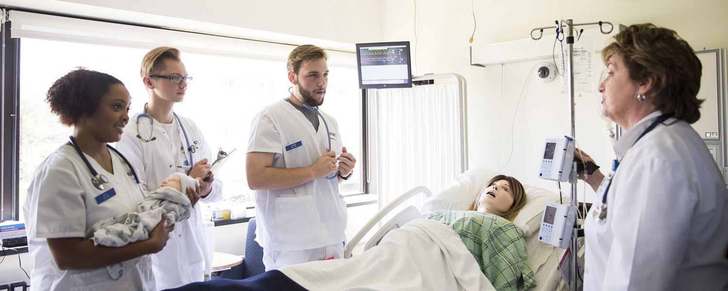 Mary Bacha (right), a lecturer in Kent State University's College of Nursing, instructs students in the Olga A. Mural Simulation Lab located in Henderson Hall.