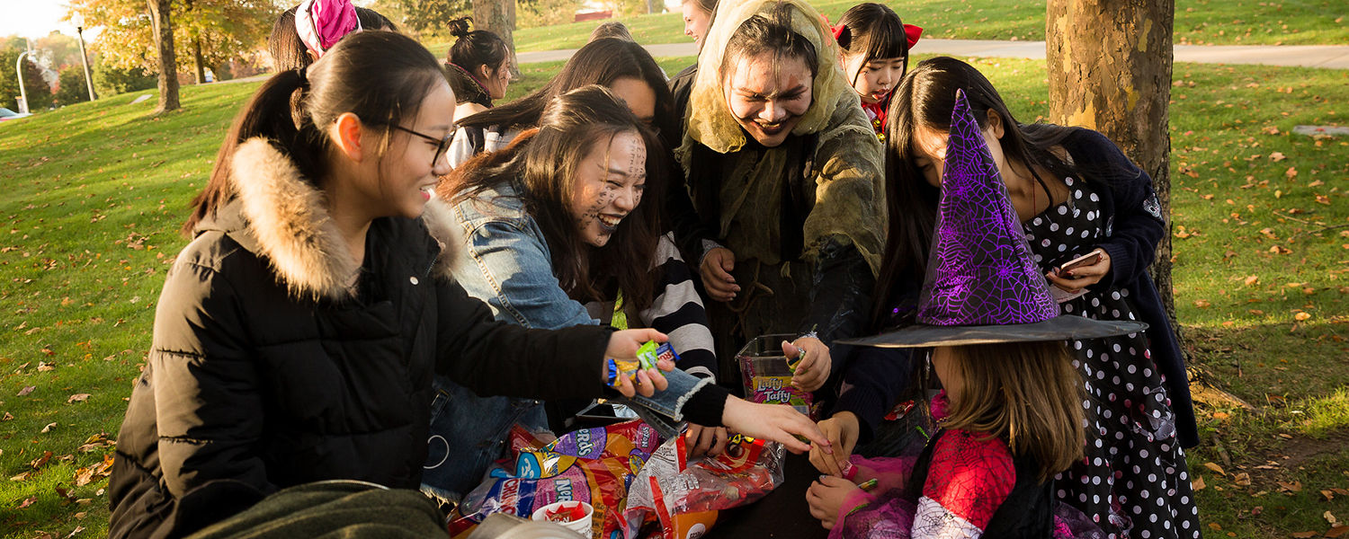 International students at Kent State Stark celebrate Halloween for the first time, handing out candy to children.