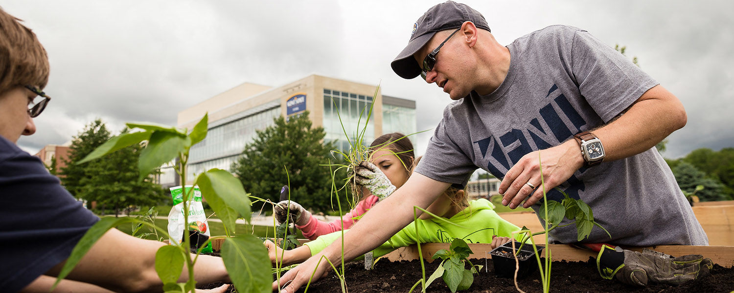 Chris Post, Ph.D., associate professor of geography, works with others on the Kent State University at Stark campus garden.