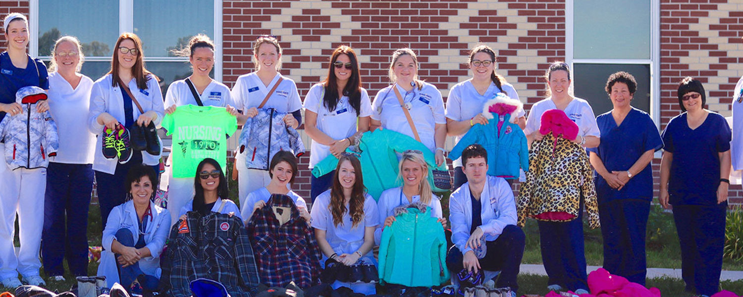 The Kent State University team shows off some of the winter clothing items donated to Lakota children living in the Pine Ridge Dormitory.