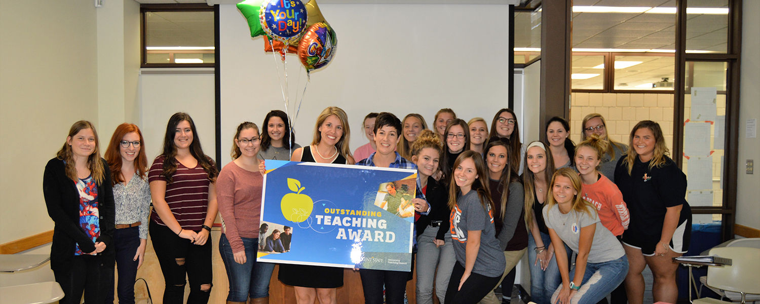 Rochelle Hostler (on the right, holding the sign), early childhood educator at Kent State University, celebrates with her students after being notified of her Outstanding Teaching Award.
