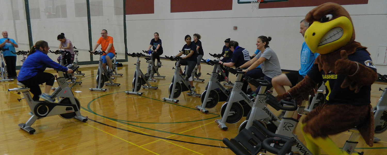 Kent State University employees and mascot Flash participate in a spin bike workout session at the Student Recreation and Wellness Center during the On the Move kickoff event.