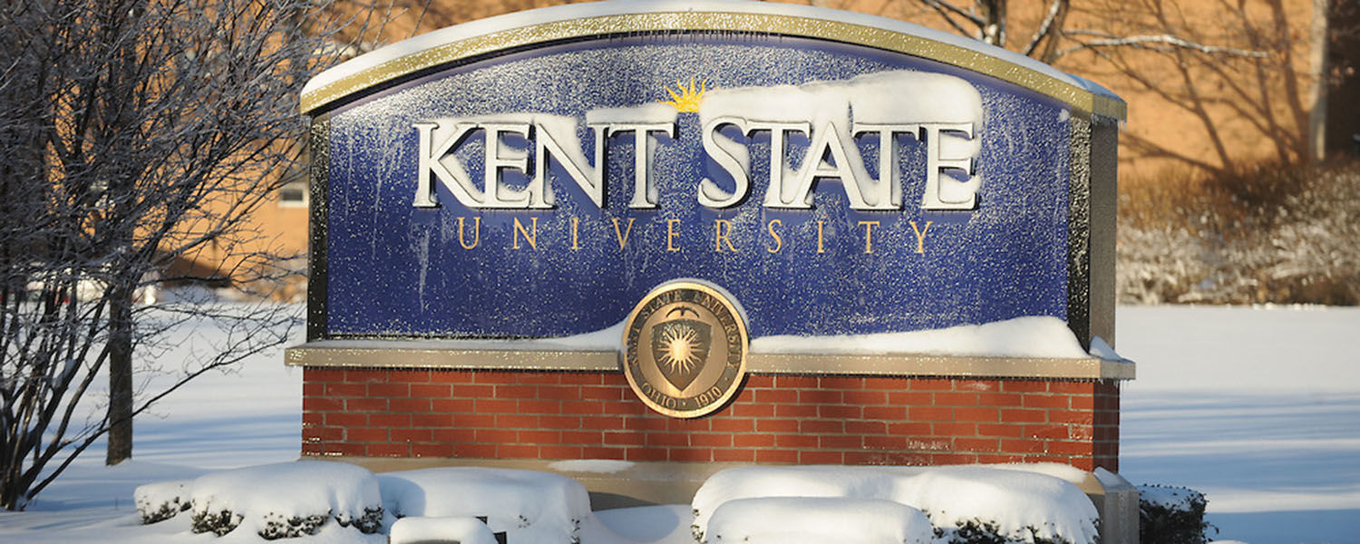 A Kent State University sign is covered in snow. The university's annual winter weather advisory serves as a guide for members of the Kent State community.