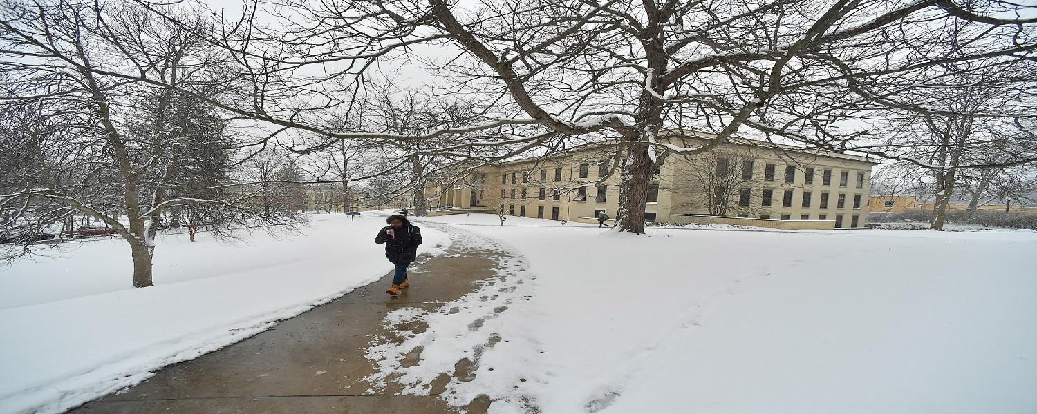 A student walks on the Kent Campus on a winter day.