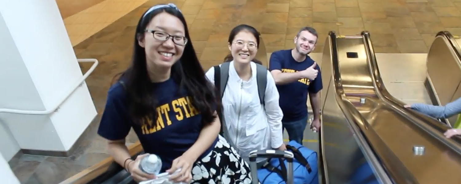International students smile for the camera as they arrive to a warm welcome from Kent State volunteers.