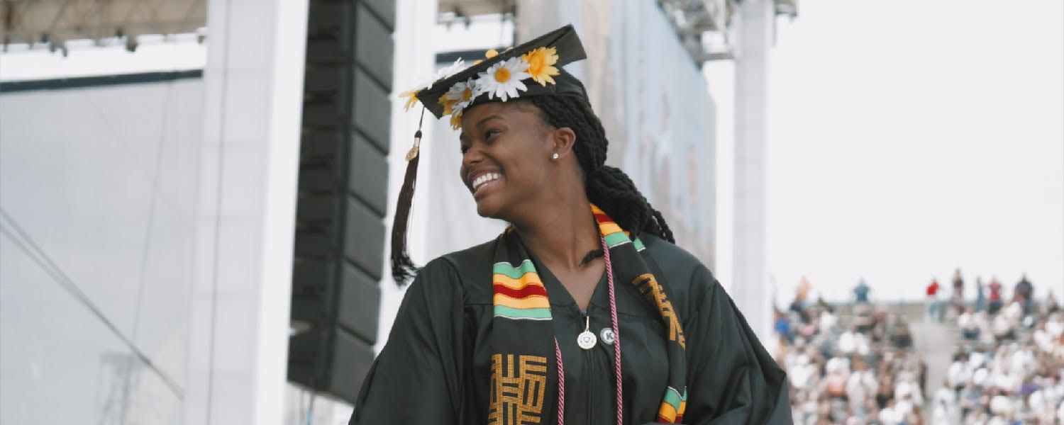 A Kent State University graduates is all smiles during the One University Commencement on May 12.