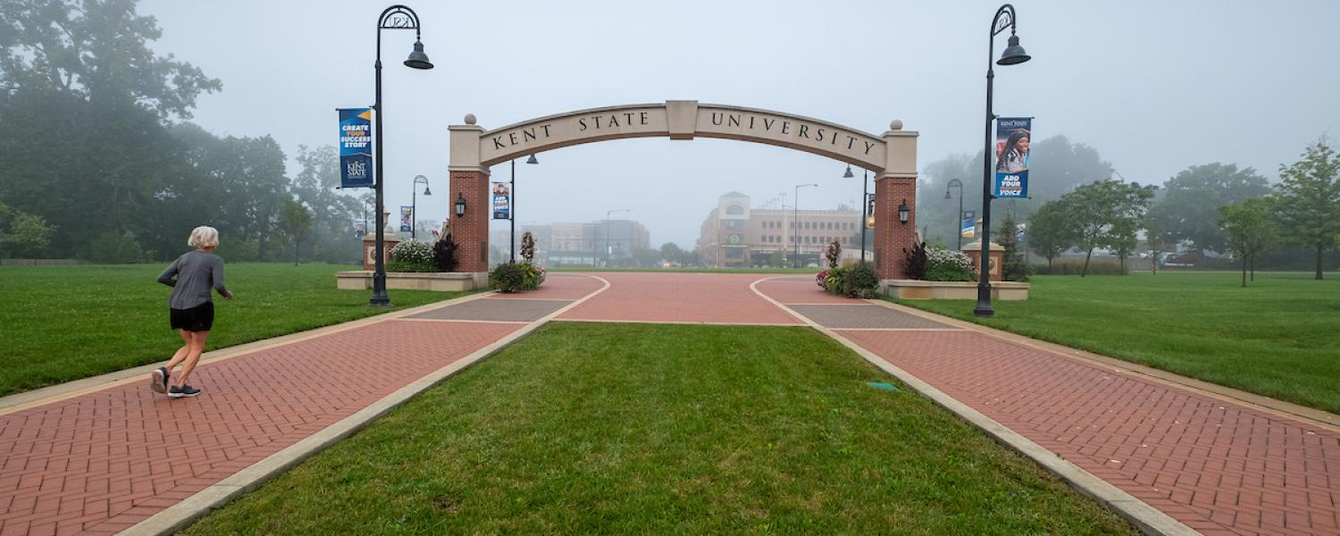 A runner strides down the Esplande during a foggy morning heading toward Kent State's campus