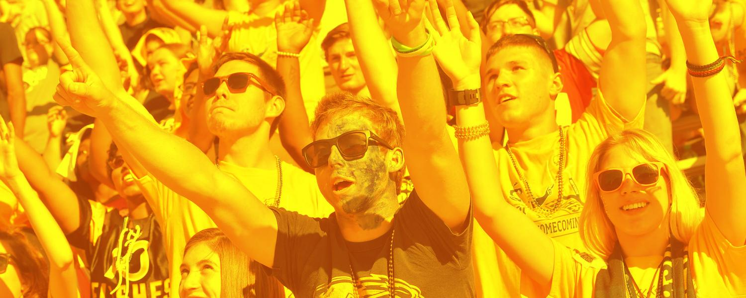 Kent State students and alumni in the crowd, cheering on with a gold filter over top the photo