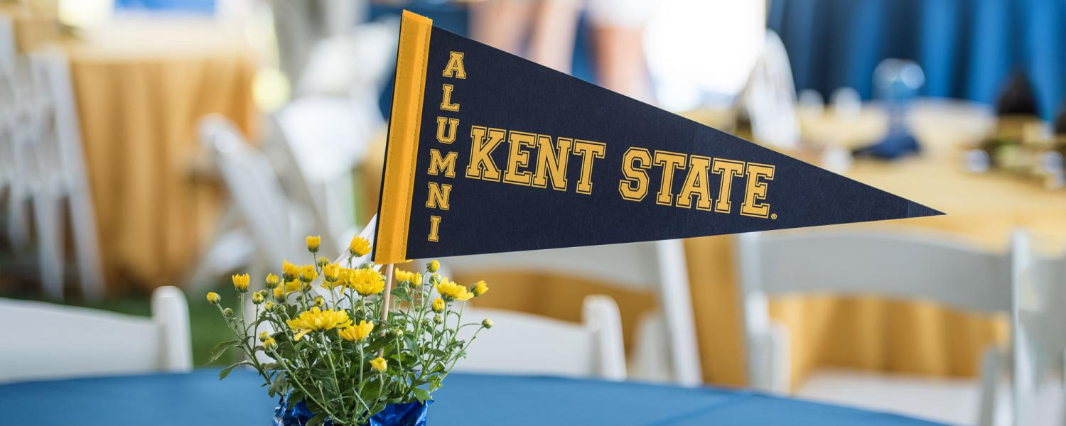 Kent State Alumni pennant on a table with flowers
