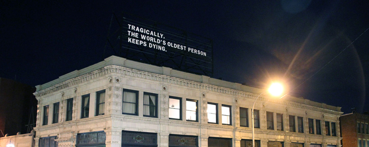 "Lenka Clayton, An Everyday Tragedy, 2016, A building with a billboard on top that reads in white letters ""Tragically, the world's oldest person keeps dying."""