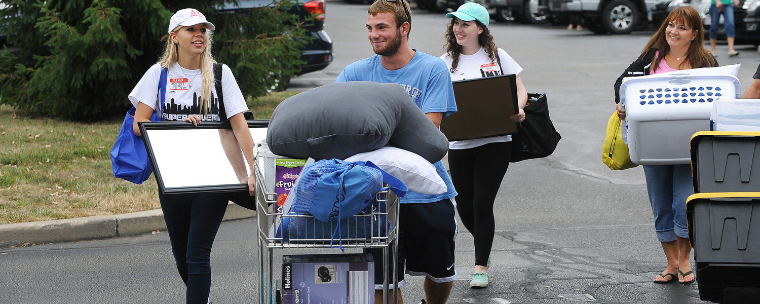 Student and movers carrying furniture and boxes