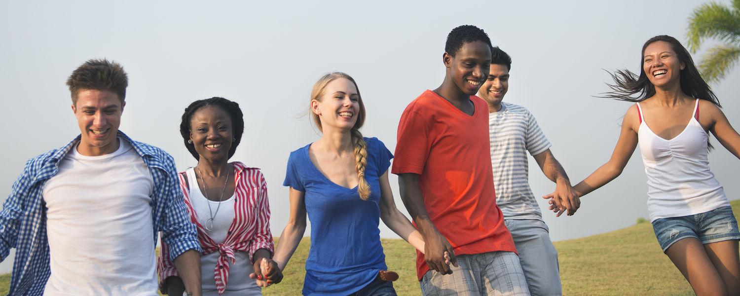 group of students cheerfully walking together outside holding hands
