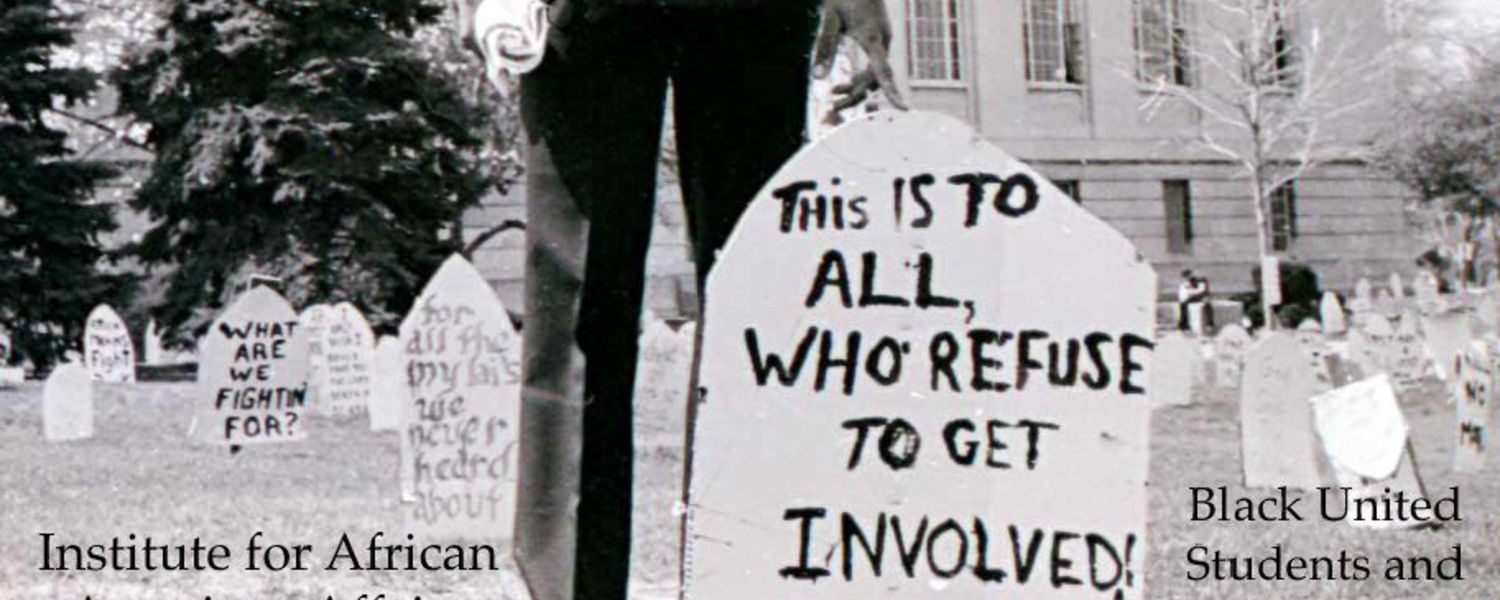 Silas Ashley cica 1967 stands behind grave marker created by Black Students to protest the war.