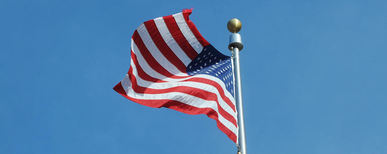 American flag on a flag pole against blue sky