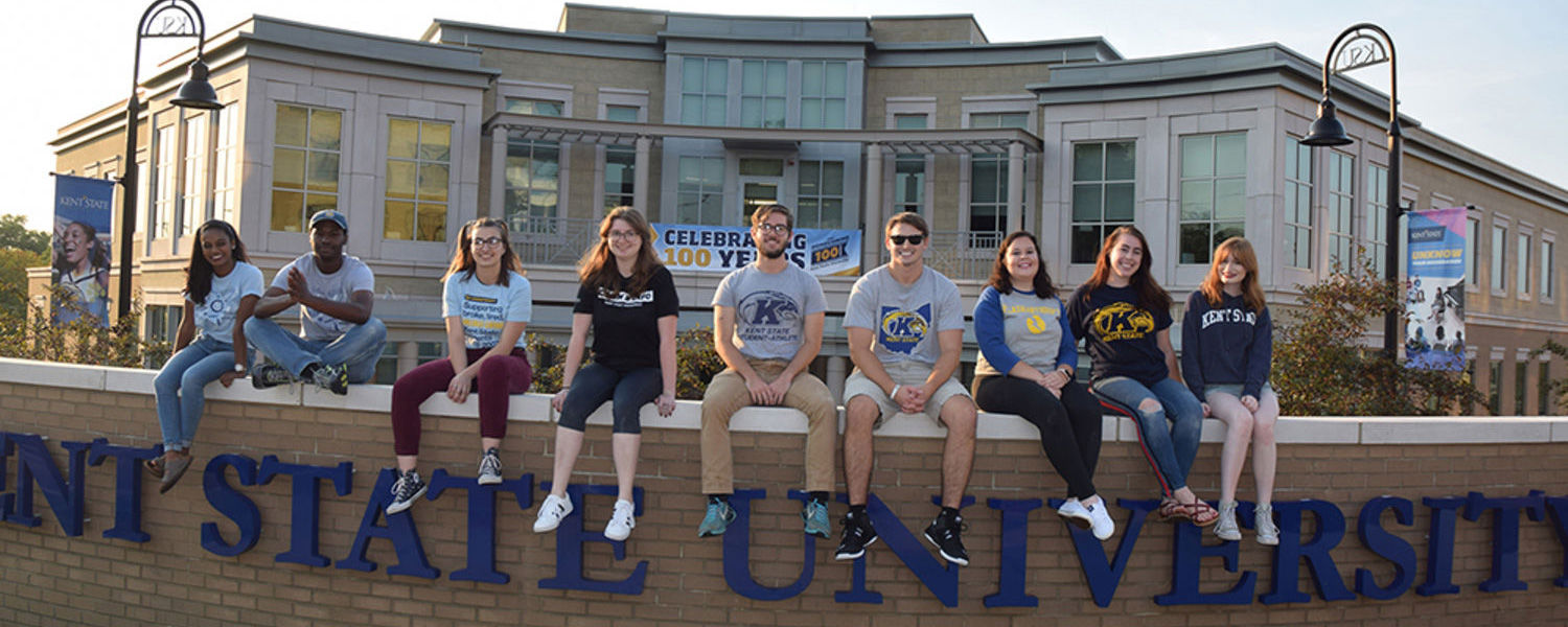 Flashanthropy members sitting on a Kent State University ledge in front of Alumni building