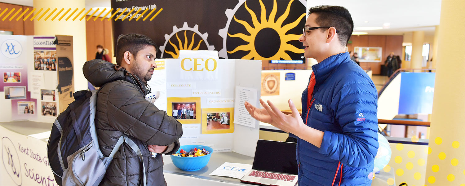 Students conversing about a CEO based club at the Student Organization Fair