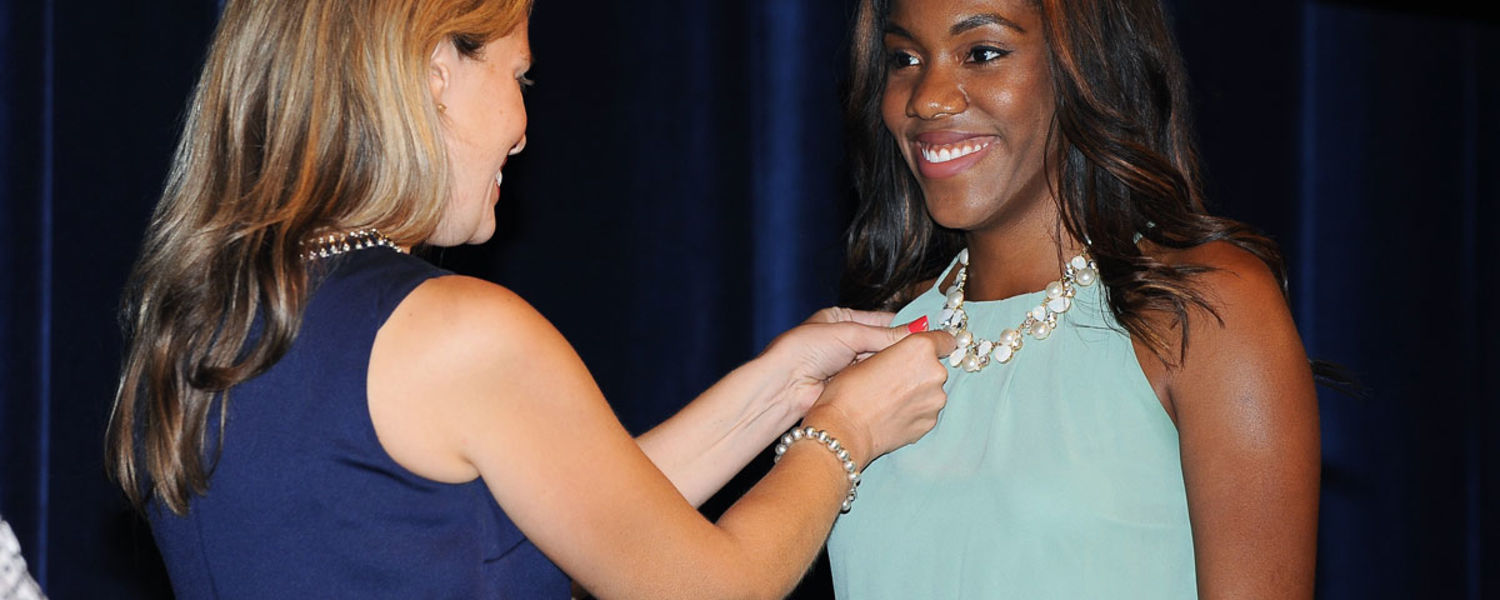 A graduate of the nursing program getting pinned by her instructor during the Convocation pinning ceremony