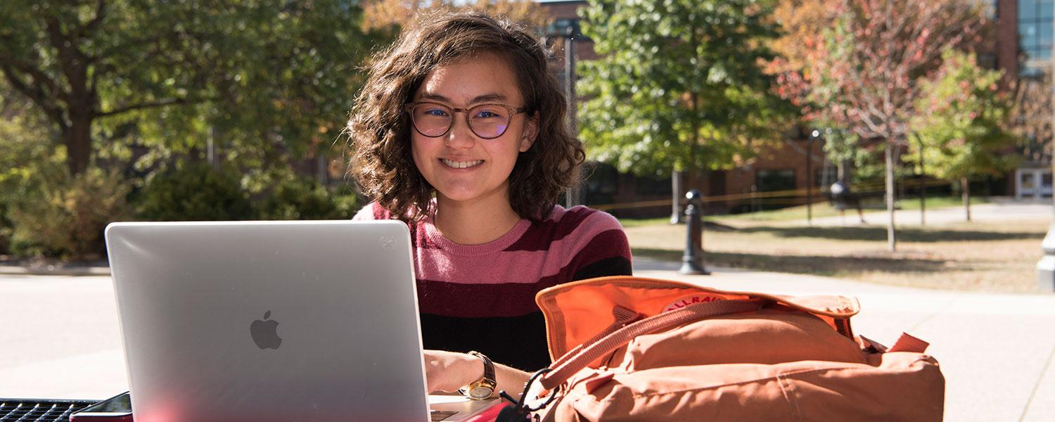 A smiling student working outside on a laptop