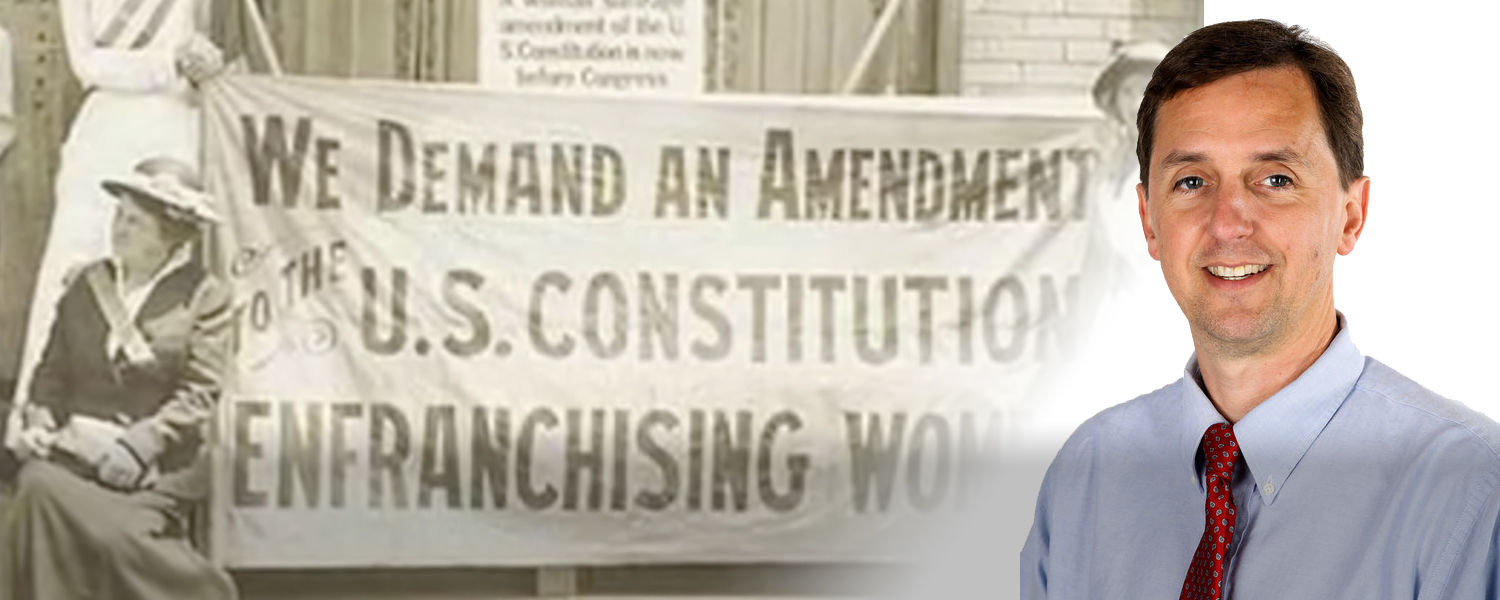 Women stand with a banner about voting rights